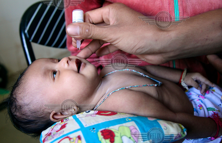 A health worker gives an oral immunisation to a baby at Preak Krabao health centre in the village of Preak Krabao.