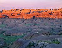 SDBD_027 - USA, South Dakota, Badlands National Park, North Unit, Sunrise light reddens eroded, sedimentary formations at Changing Scenes Overlook.