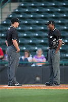 Umpires Tom West (left) and Darrell Roberts meet at home plate prior to the South Atlantic League game between the Lexington Legends and the Hickory Crawdads at L.P. Frans Stadium on April 29, 2016 in Hickory, North Carolina.  The Crawdads defeated the Legends 6-2.  (Brian Westerholt/Four Seam Images)