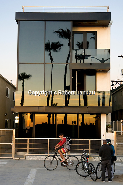 A bicylcist rides past a beach house refelcting the setting sun at Venice Beach, CA