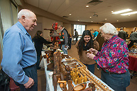 NWA Democrat-Gazette/BEN GOFF @NWABENGOFF<br /> Jimmy Hylton looks on as his wife Vera Hylton of Springdale shows a carved wood piece to Leticia Cortez Saturday, Jan. 12, 2019, during the annual collectors day 'Cabin Fever Reliever' at the Shiloh Museum of Ozark History in Springdale. Vera Hylton was showing some pieces she carved herself as well as those she has collected from others. Dozens of local collectors set up tables showcasing their collections of such various things as kitchen utensils, coins, buttons, hand fans, fossils woodcarving and much more.