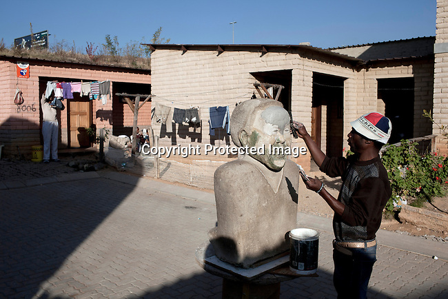 ALEXANDRA TOWNSHIP, JOHANNESBURG, SOUTH AFRICA : Artist George Rangwanasha makes a Mandela sculpture outside his home in Alexandra, a poor township in Johannesburg, South Africa. (Photo by Per-Anders Pettersson)