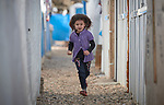 A Yazidi girl runs between shelters in a camp for internally displaced persons at Dawodiya in Iraq's Kurdistan region. More than 600 Yazidi families living in the camp escaped from their communities in the Sinjar region during the attempted genocide by the Islamic State group. Although ISIS was militarily defeated in 2017, camp residents say it's still not safe to return home, nor do they have sufficient resources to rebuild their homes.<br /> <br /> The Lutheran World Federation, a member of the ACT Alliance, provides water, sanitation, garbage collection, and psycho-social support for the families in the camp.