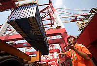 A dock worker directs the loading of a container onto a truck at the new Qianwan container terminal of the Qingdao Port in Qingdao, China..