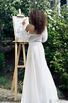 Beautiful woman sumi-e artist with an easel painting outdoors in a green garden in sunlight wearing a sheer white gown Image © MaximImages, License at https://www.maximimages.com