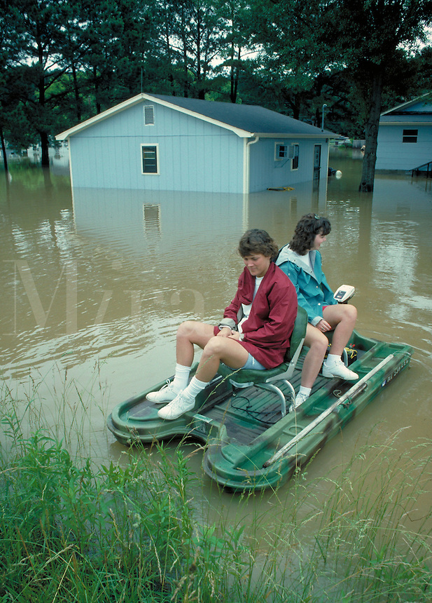 two women riding in small skiff in flood damaged area. women. Tupelo Mississippi USA.