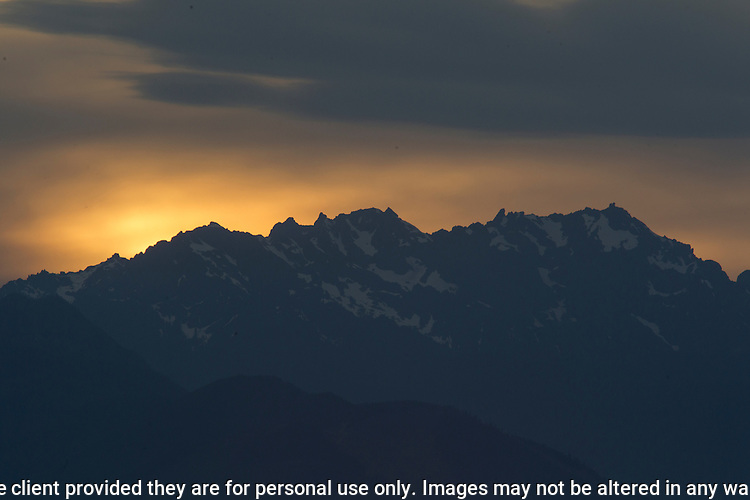 Hazy clouds cover the Olympic mountains doing a sunset over Washington's Olympic National Park. The Olympic Mountains is a year-round destination. In summer, visitors come for views of the Olympic Mountains, as well as for superb hiking.   ©2016. Jim Bryant Photo. All Rights Reserved.