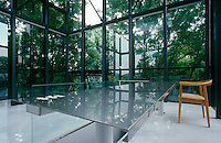 A stainless steel table lines one side of the staircase opening into the salon, a double-height conservatory at the rear of the house in a woodland setting