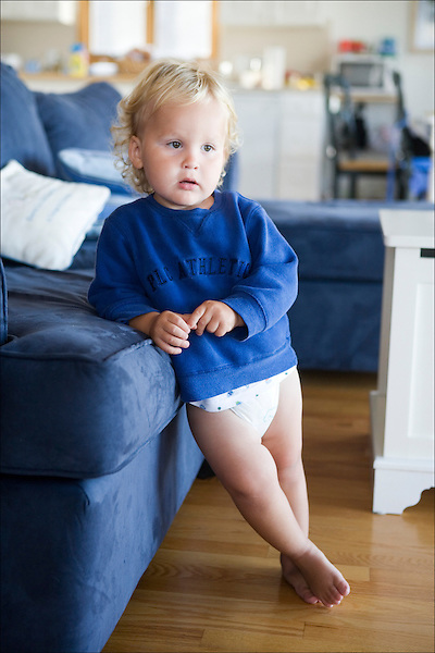 little boy leaning against sofa in beach house wearing blue sweatshirt and diapers