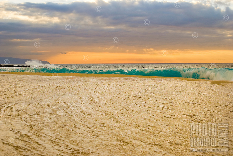 Shorebreak crashes on the beach during a sunset at Ke Iki beach, on the North Shore of Oahu. Kaena Point can be seen in the background.