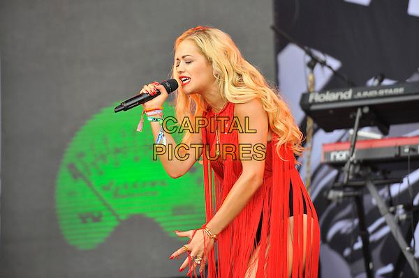 Rita Ora <br /> performing at Glastonbury Festival, Worthy Farm, Pilton, Somerset, <br /> England, UK, 28th June 2013.<br /> live on stage music gig half red tassels dress hotpants singing microphone black pants side fringed<br /> CAP/MAR<br /> &copy; Martin Harris/Capital Pictures