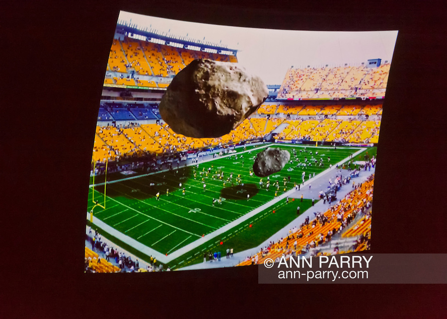 Garden City, New York, U.S. November 21, 2013. An illustration, with art by Michael Carroll, showing the relative sizes of the 2013 DA14 asteroid, half as big as a football field and large enough to level a city, and the Chelyabinsk Meteor which struck Russia, was shown during lecture by NASA Astronaut R. Schweickart, 1969 Apollo 9 Lunar Module LM Pilot, at Legends of Air and Space event at Cradle of Aviation Museum on Long Island. Schweickart, a co-founder of the Association of Space Explorers and of the B612 Foundation, spoke on the importance of defending Earth from asteroid impacts.