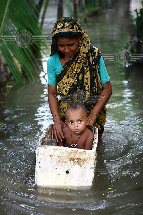 A mother transports her child through the floodwaters. Thousands of people were displaced in Shyamnagar Upazila, Satkhira district after Cyclone Aila struck Bangladesh on 25/05/2009, triggering tidal surges and floods..