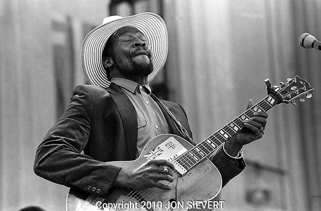 Taj Mahal, Bread & Roses Festival, Oct 4,1980 50-6-14A. Internationally recognized blues musician with two Grammy Awards to date who folds various forms of world music into his offerings. A self-taught singer-songwriter and film composer who plays the guitar, banjo and harmonica (among many other instruments), Mahal has done much to reshape the definition and scope of blues music over the course of his almost 50-year career by fusing it with nontraditional forms, including sounds from the Caribbean, Africa and the South Pacific.