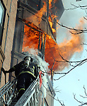 (Boston Ma 020114) A Boston firefighter from Ladder 15, climbs towards the fire on the  5th floor as fire extends to the sixth floor in the rear at 31 Massachusetts  Ave, during the fire that went to seven alarms. (Jim Michaud  Photo) For Sunday