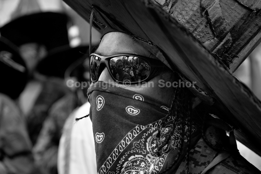 An Indian, wearing a cardboard hat and black glasses, performs during the Inti Raymi (San Juan) festivities in Cotacachi, Ecuador, 24 June 2010. 'La toma de la Plaza' (Taking of the square) is an ancient ritual kept by Andean indigenous communities. From the early morning of the feast day, various groups of San Juan dancers from remote mountain villages dance in a slow trot towards the main square of Cotacachi. Reaching the plaza, Indians start to dance around. They pound in synchronized dance rhythm, shout loudly, whistle and wave whips, showing the strength and aggression. Dancers from either the upper communities (El Topo) or the lower communities (La Calera), joined in respective coalitions, seek to conquer and dominate the square and do not let their rivals enter. If not moderated by the police in time, the high tension between groups always ends up in violent clashes.