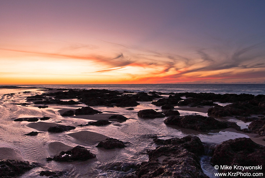 Colorful sunset over the rocky shoreline of Keiki Beach, Oahu