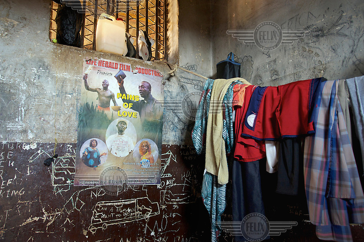 The interior of a cell that houses up to 10 male inmates at Bo Prison. A Nollywood film poster for 'PAINS OF LOVE' hangs beside clothes on a line and graffiti that reads 'I AM A LIBERIAN I WANT TO GO HOME'.