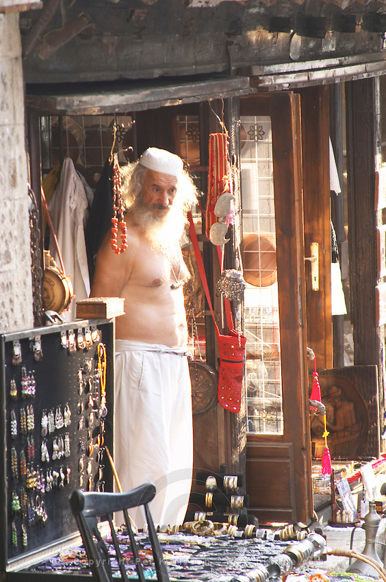 The busy old market bazaar street Onescukova with lots of tourist craft and art shops and street merchants. Souvenir merchant dressed in white pants and naked torso, with long beard and hair and white cap. Historic town of Mostar. Federation Bosne i Hercegovine. Bosnia Herzegovina, Europe.
