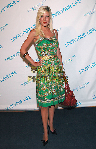 "TORI SPELLING.American Eagle Outfitters' ""Live Your Life Contest"" winners at the Union Square flagship store in Manhattan, New York, New York..July 27th, 2005  .Photo Credit: Patti Ouderkirk/AdMedia.full length red leather bag green pattern print dress gold belt hand on hip braacelet.www.capitalpictures.com.sales@capitalpictures.com.© Capital Pictures."
