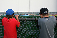 July 4, 2009:  Two young fans peak through a hole in the outfield fence to catch some action during the 4th of July celebration in hopes of catching a home run ball - both had tickets to the game at Dwyer Stadium in Batavia, NY.  The Muckdogs are the NY-Penn League Short-Season Class-A affiliate of the St. Louis Cardinals.  Photo By Mike Janes/Four Seam Images