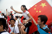 Spectators waving Chinese flags watch the Olympic torch pass by during the Nanjing, China, leg of the 2008 Olympic Torch Relay.  .