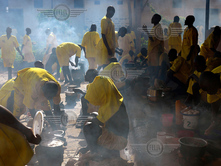 Inmates cooking food, provided by their families, in a courtyard in Kigo Prison, a high security facility which accommodates 1,175 prisoners.
