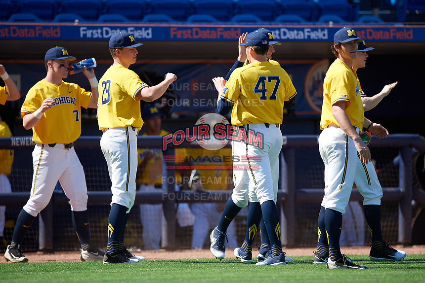 Michigan Wolverines starting pitcher Tommy Henry (47) is congratulated by teammates, including Blake Beers (29), in between innings, during a game against Army West Point on February 17, 2018 at Tradition Field in St. Lucie, Florida.  Army defeated Michigan 4-3.  (Mike Janes/Four Seam Images)