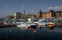 Boats moored at the marina in Neuchatel harbour, with  museum-postoffice and hotels in the background. Lake Neuchatel , Switzerland.