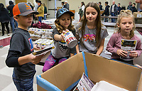 NWA Democrat-Gazette/BEN GOFF @NWABENGOFF<br /> Bear Ortega (from left), 9, sister Vivianne Ortega, 7, sister Leighton Ortega, 10, and friend Bowen Powell, 5, all First Baptist Church members, top off boxes with cranberry sauce Thursday, Nov. 28, 2019, during the annual Thanksgiving meal distribution at the First Baptist Church Olive Street campus in Rogers. <br /> <br /> Paul Olinger, a church member who helped coordinate the meal, said the event started 20 years ago 'As an outreach of the church to show the love of Christ in the community'. Volunteers from the church and the community cooked, packaged and delivered boxed meals that included ham, green beans, mashed potatoes and deserts. <br /> <br /> Open to anyone, a line wrapped around the room as families picked up boxes of food to take home, but Olinger estimates that 98 percent of the meals are delivered by volunteers.
