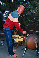 FREMONT -  Al Mangin barbecues hot dogs in his backyard while holding a can of Hamms beer in Fremont, California in 1985. (Photo by Brad Mangin)