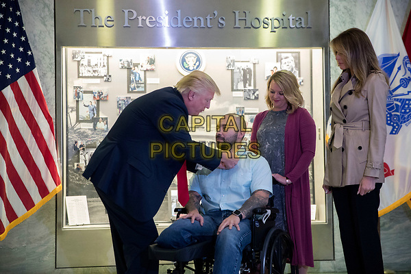 US President Donald J. Trump (L), with First Lady Melania Trump (R), awards Sergeant First Class Alvaro Barrientos (2-L), with his wife Tammy Barrientos (2-R), the Purple Heart to him during a visit to Walter Reed National Military Medical Center in Bethesda, Maryland, USA, 22 April 2017. Sergeant First Class Alvaro Barrientos was recently injured in Afghanistan while deployed and for the wounds he sustained, he is receiving the Purple Heart.<br /> CAP/MPI/RS<br /> &copy;RS/MPI/Capital Pictures
