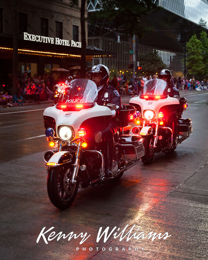 Seattle Motorcycle Police Force clearing street crowds before Seafair Torchlight Parade 2015, Seattle, Washington State, WA, America, USA.