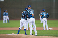 Ogden Raptors first baseman Dillon Paulson (14) hugs starting pitcher Jose Chacin (26) prior to a Pioneer League game against the Billings Mustangs at Lindquist Field on August 17, 2018 in Ogden, Utah. The Billings Mustangs defeated the Ogden Raptors by a score of 6-3. (Zachary Lucy/Four Seam Images)