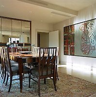 A large abstract artwork dominates one wall of the dining room