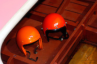 The old and the new: left, an old style helmet that had to be painted international orange for boat racing visibility (and almost everything gets painted on it) and right a modern helmet from the same company.