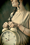 Young woman holding large alarm clock