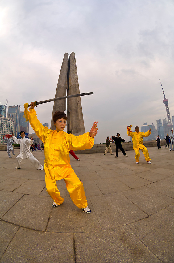 Chinese people practicing tai chi with swords in the early morning in Huangpu Park , Shanghai, China