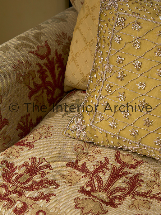 A cushion embroidered in silver thread on a background of dull gold is arranged on an armchair covered in a red and beige floral linen