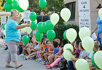 NWA Democrat-Gazette/DAVID GOTTSCHALK  Principal Tracy Bratton distributes balloons to kindergarten students at Asbell Elementary School in Fayetteville before participating in a balloon release Friday, August 7, 2015. Three classes of kindergarten students participated in the annual release marking the launch of their academic careers.