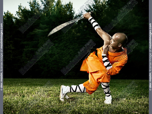 Monk practicing Shaolin broad sword Kung Fu weapon form outdoors