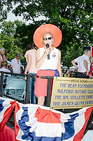 A woman announces marchers from the stage in the 4th of July Parade in Amherst, New Hampshire, on Thu., July 4, 2019.