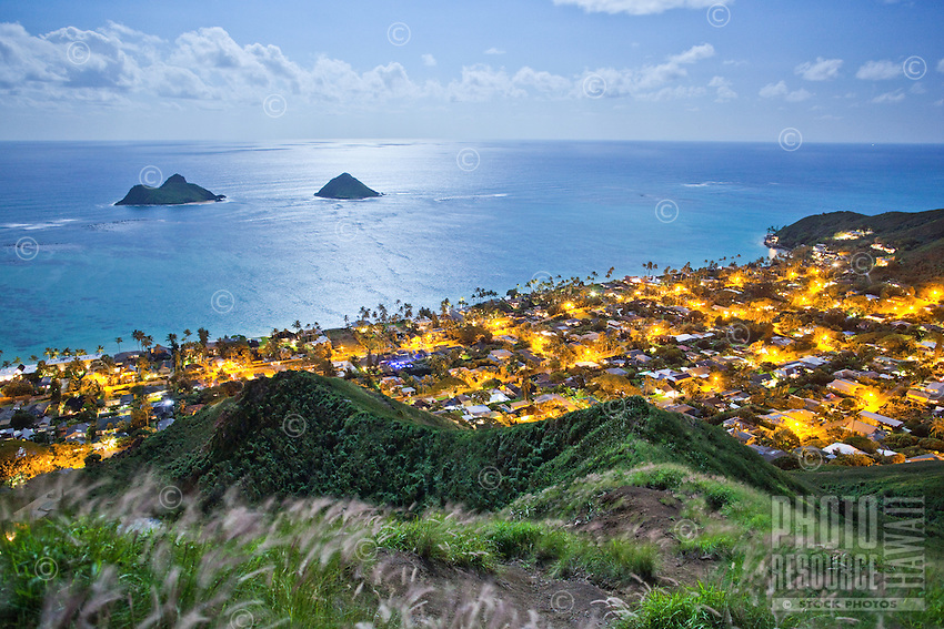 The top of the Pillboxes hike offers a view of light from a full moon reflecting on the ocean over the Mokulua Islands; street lights glow amongst the residences of Lanikai, O'ahu.