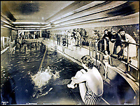 "BNPS.co.uk (01202 558833)<br /> Pic:    CanterburyAuctionGalleries/BNPS<br /> <br /> The indoor First Class swimming pool had staggered depths ending with a shallow ""beach"" for children and a bar at the far end for parents.<br /> <br /> Remarkable photos of the iconic ocean liner SS Normandie which was like a 'floating palace' have come to light over 80 years later.<br /> <br /> The giant 1,000ft long French passenger ship was the largest of her type in the world and won the coveted 'Blue Riband' for the fastest crossing of the Atlantic.<br /> <br /> English photographer Percy Byron's photos show the liner's luxurious 'Art Deco' interior with its chandeliers and pillars of Lalique glass.<br /> <br /> The vessel, which launched in 1935, even boasted its own swimming pool and a gym where young women can be seen doing aerobics while a man in a suit trains with a punch bag."