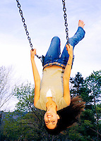 Beautiful young brunette swinging upside down at the park.