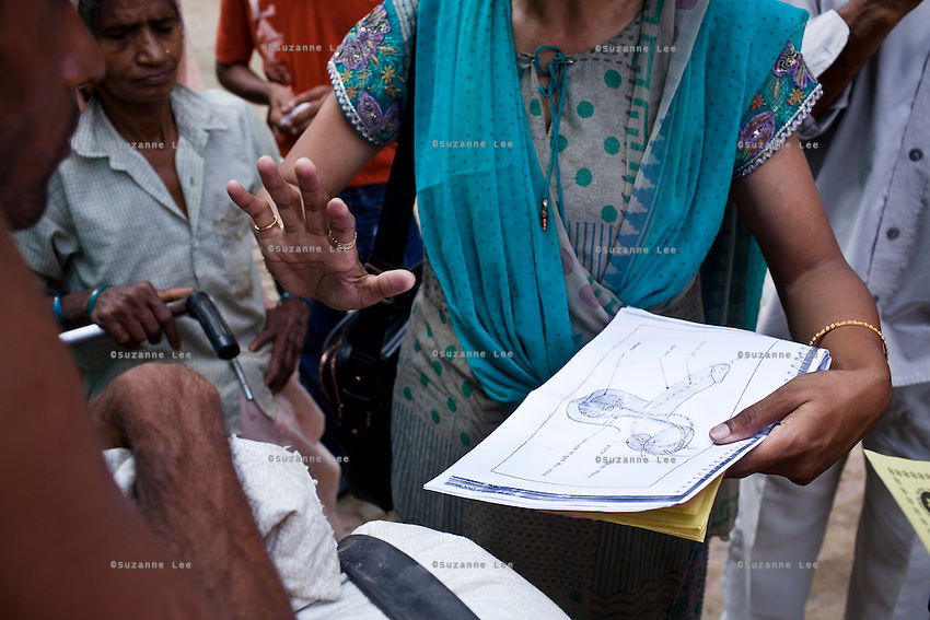 Jagroshan Sharma (aged 36, unseen) approaches random villagers from Shahpurjat village with Dr. Meenal Mehta (in blue), who is in charge of the USAID NSV projects in Ghaziabad, Uttar Pradesh, India. After doing NSV himself, he has been a star link worker introducing about 5 NSV cases per month since he started working part time under the tutelage of Dr Mehta. Jagroshan had chosen to do a non-scalpel vasectomy (NSV) for many reasons. He wanted to be an equal partner in the relationship, knew that NSV was less complicated and will not put his wife through numerous problems, and wants his two children to do well in life and study in English medium schools despite his modest earnings. Photo by Suzanne Lee / Panos London