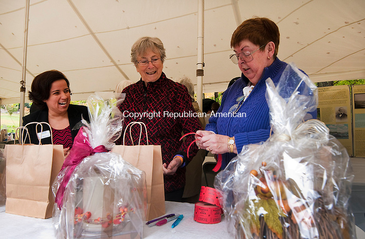 WATERBURY, CT-101114JS01- Marion Hubbard, right, Board President for Brass City Harvest, sells raffle tickets to volunteer gardner Gen Delkescamp, center, and Maybeth Morales-Davis, Development Associate with the Connecticut Community Foundation, left, during the Brass City Harvest's Harvest Luncheon Saturday at Fulton Park in Waterbury. The lunch consisted of locally grown food as well as a farmers market. <br />