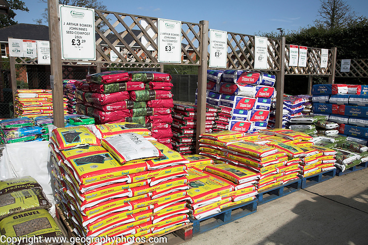Bags of compost fertiliser on pallets in a garden centre, UK