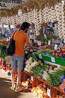 Tall young man  shopping at a fruit and vegetable stall in the Jean Talon public market or Marche Jean Talon, Montreal, Quebec, Canada