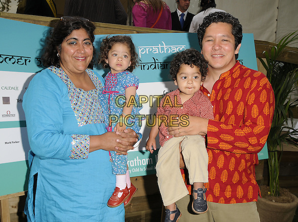 GURINDER CHADHA, KUMIKO, RONAK & PAUL MAYEDA BERGES.The Pratham Indian Summer Party, The Conservatory, Chelsea Garden, Embankment, London, England..June 28th, 2009.half length mother mom mum carrying family dad father black pinstripe trousers son daughter blue red.CAP/CAN.©Can Nguyen/Capital Pictures.
